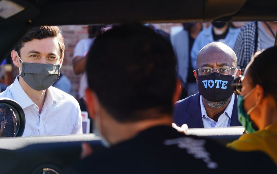 Jon Ossoff and Raphael Warnock, both wearing masks, speak to supporters who are seated in their car.