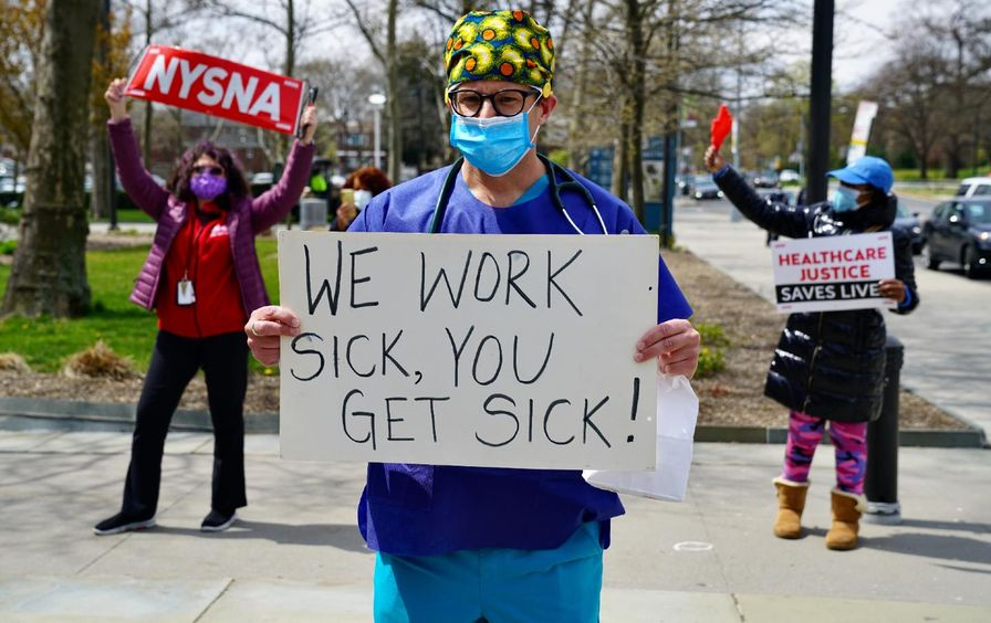 Three people protest, holding signs and wearing masks. The one in the center front holds a sign that reads