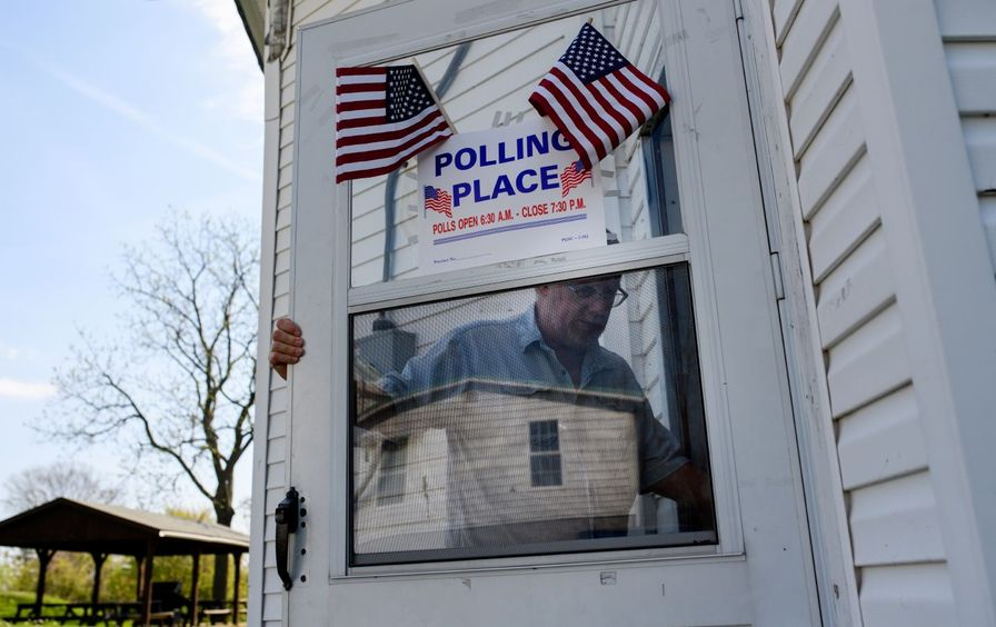 Man walks into polling place marked with American flags.