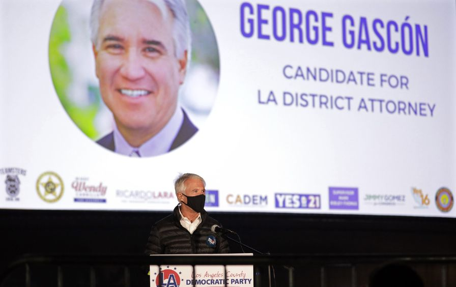 Gascón stands, wearing a mask, in front of a large projected slide with a picture of himself that reads