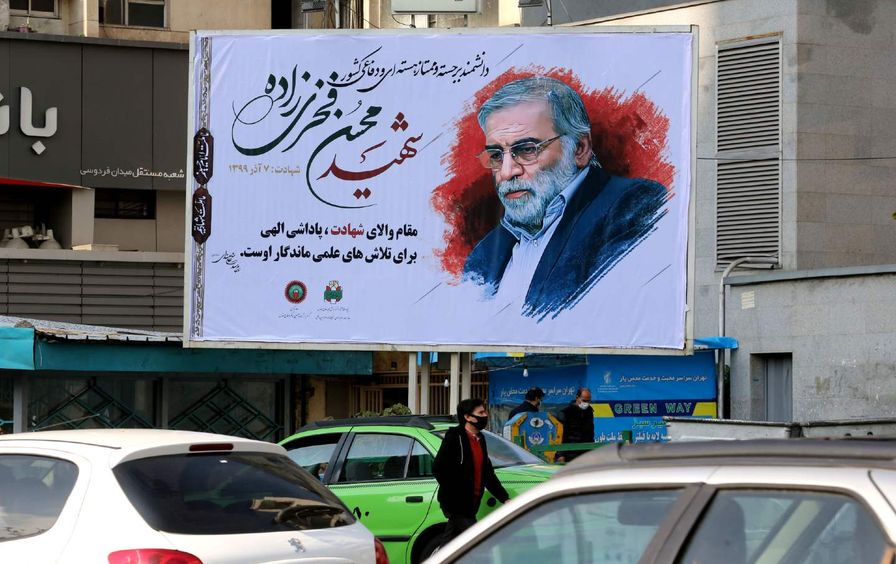 Vehicles drive by a billboard featuring Mohsen Fakhrizadeh