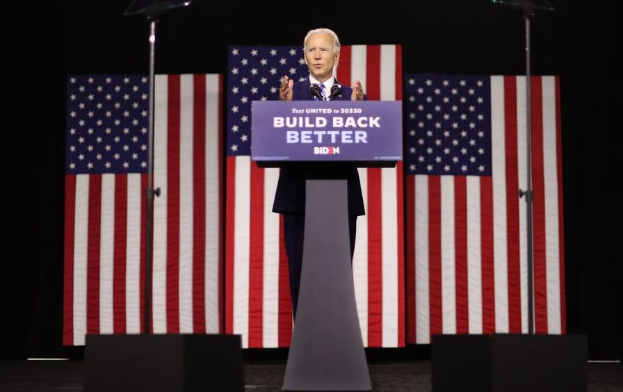 Joe Biden speaks at a podium that reads