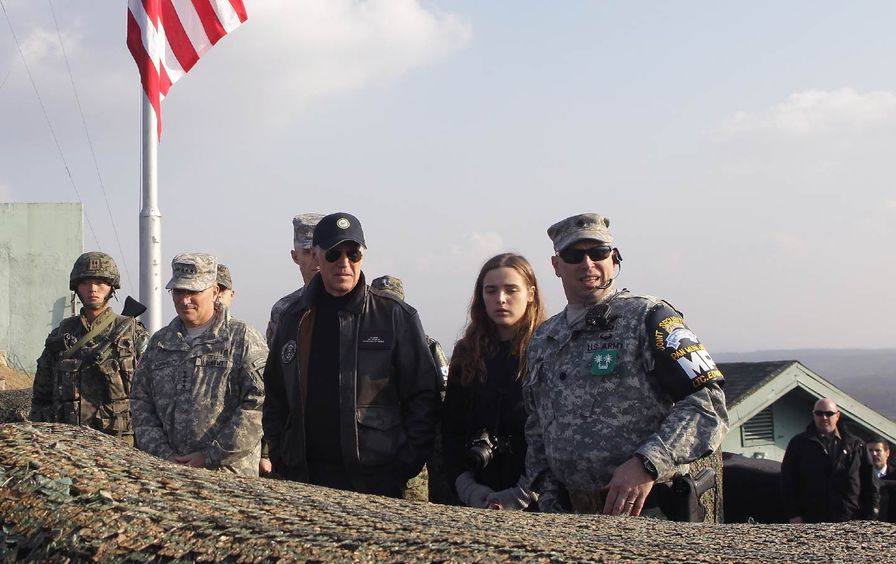 Joe Biden stands with his granddaughter and six soldiers at an Army post.