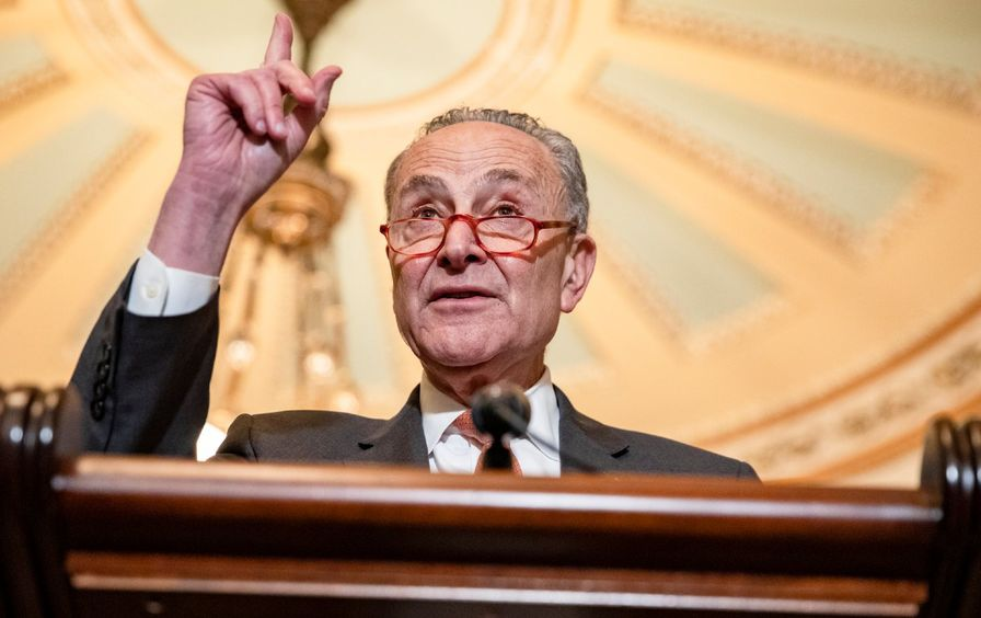 Chuck Schumer stands behind a podium, wagging a finger. He wears a suit and tie and red glasses.