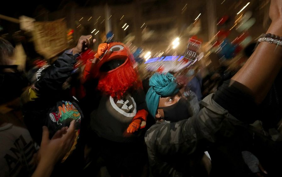 A man in a gritty costume dances with protestors.