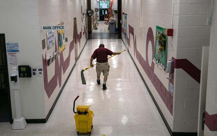 Man mopping a school hallway