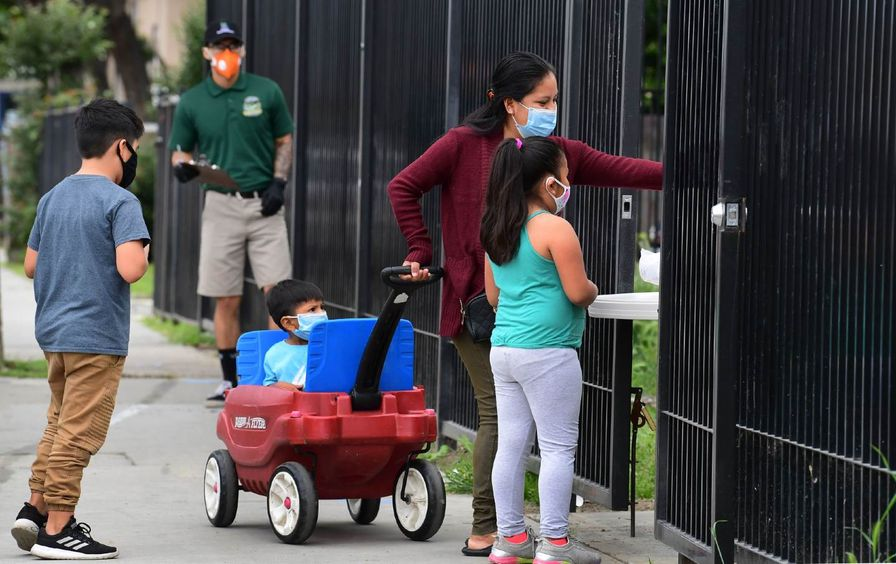 A woman with her children wearing masks, reaches out to pick up a bag of groceries.