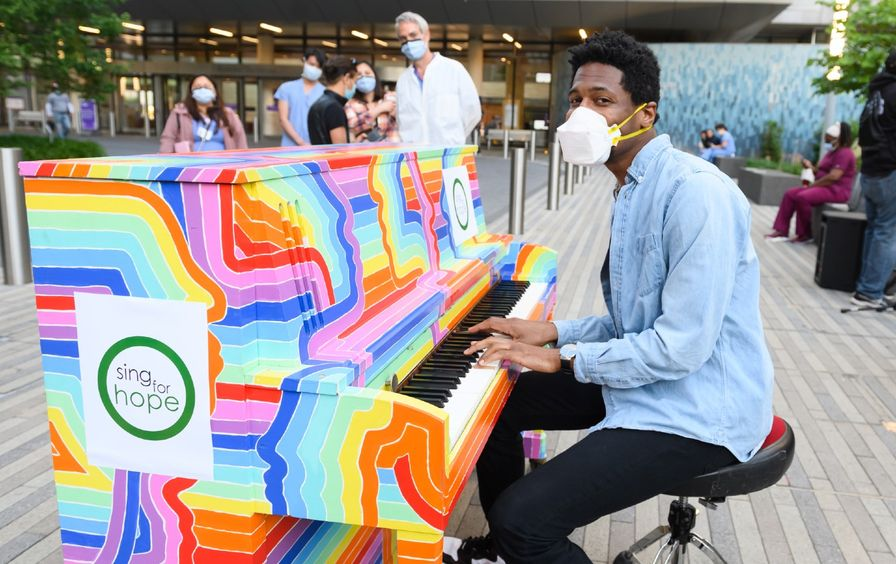 Jon Batiste plays a rainbow-colored piano outdoors as people in surgical masks walk by