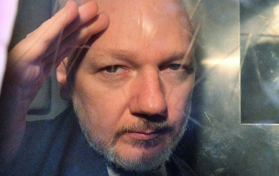 Julian Assange waves slightly with his face up close against the window of a prison van