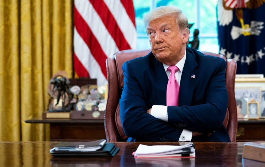 Donald Trump sits at his desk in the Oval Office, making a pouting face