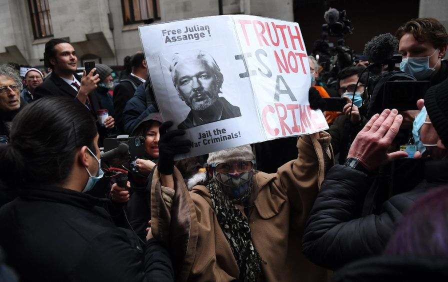 Julian Assange supporters celebrate outside, one holding a sign that says