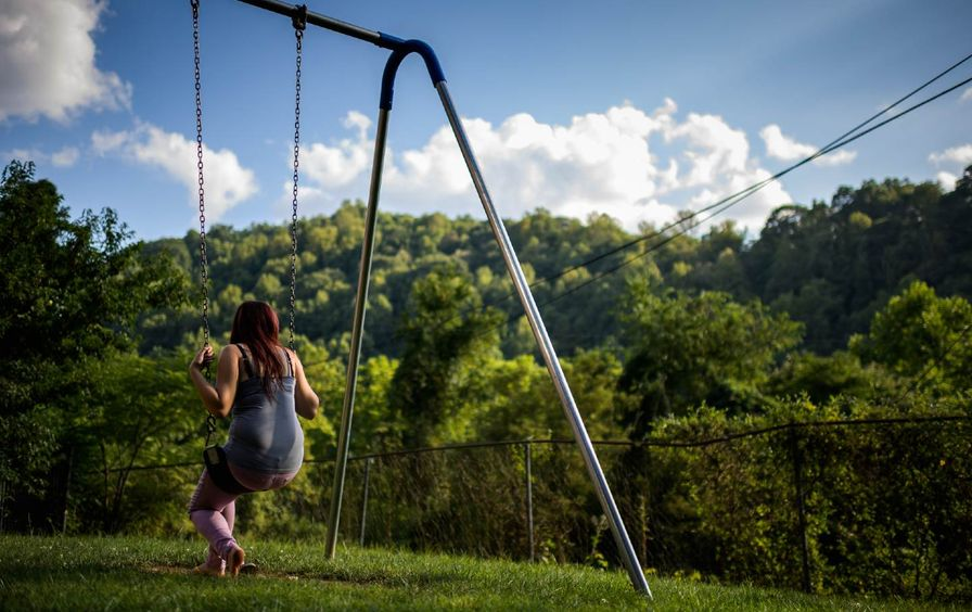 fifteen year old foster girl who just arrived sits on the swing at the Paul Miller Home