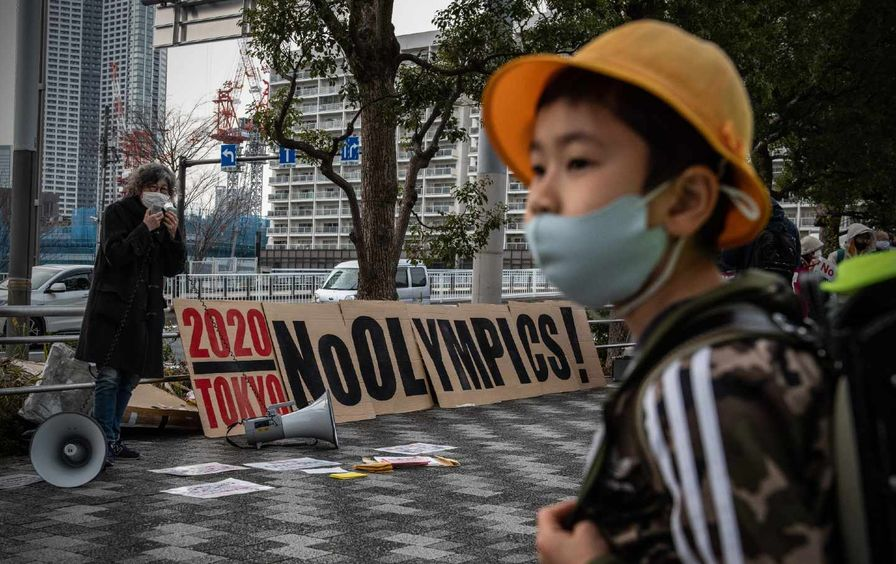 """A young schoolboy in a mask, wearing a black jacket with three white stripes and an orange bucket hat, walks past a banner saying """"No Olympics"""" during a protest calling for the Tokyo Olympics to be canceled."""