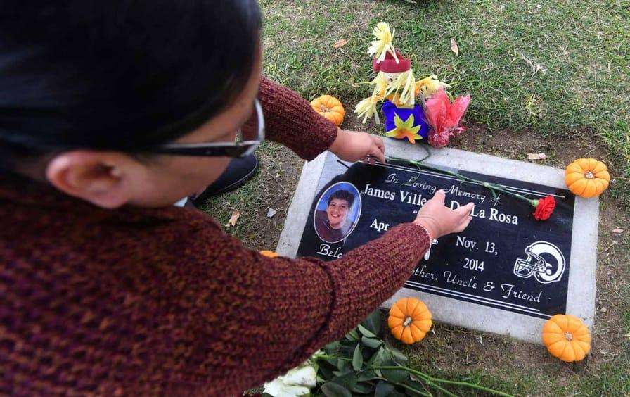 Mother of James De la Rosa places flowers on her son's grave