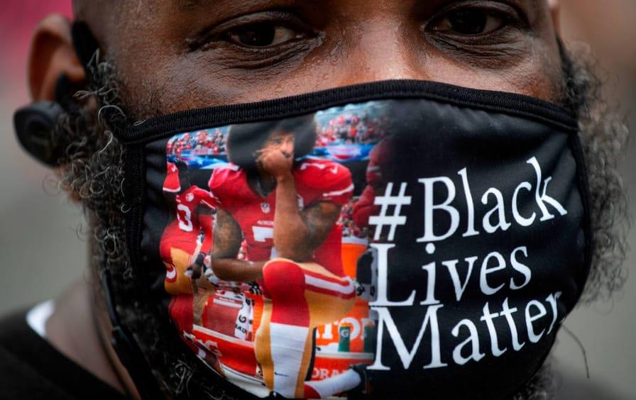 A Black man wearing a mask with Colin Kaepernick kneeling and the words #BlackLivesMatter