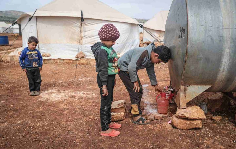 Syrian children draw from a water container at a refugee camp in the village of Kafr Aruq.