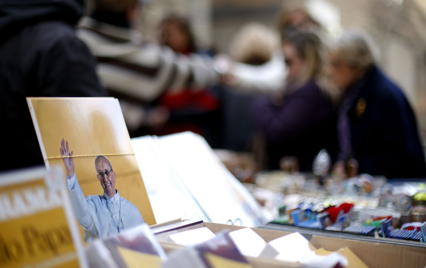 Prints of Pope Francis are seen in a newspaper kiosk near the Vatican.