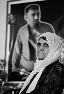 Fatima Ahmed Salih in front of a portrait of her son, Sherzad Taha
