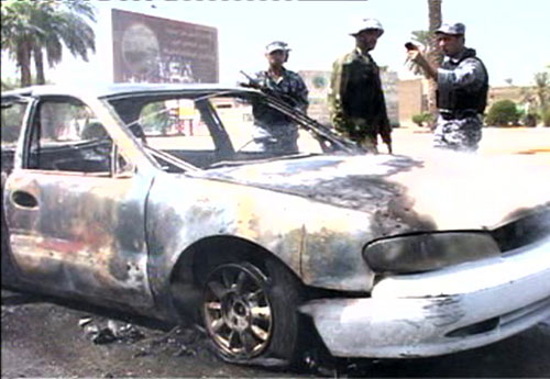 Iraqi police stand near the al Rubia'ys' vehicle after the shooting.