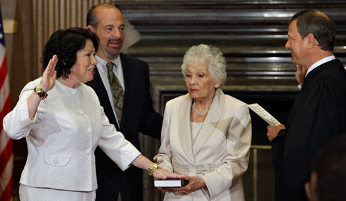 Sonia Sotomayor takes the oath from Chief Justice John Roberts to become the Supreme Court's first Hispanic justice and only the third woman in the court's 220-year history, in Washington, Saturday, Aug. 8, 2009. She is joined by her brother, Juan Luis Sotomayor, and her mother Celina Sotomayor.  [AP Images]