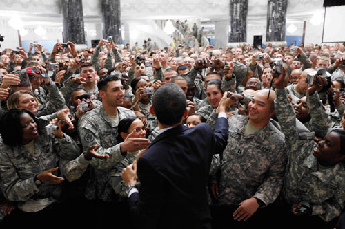 On the tail end of his trip abroad, Obama makes a surprise visit to US troops stationed in Camp Victory in Baghdad, Iraq. He thanks them for their sacrifice and pledges to turn Iraq over to the Iraqis. (AP Images)