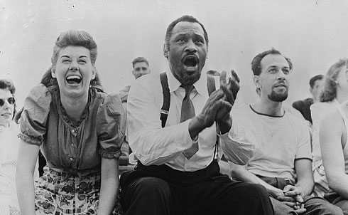 Robeson was perhaps the most all-around talented American of the twentieth century. He was an internationally renowned concert singer, actor, college football star and professional athlete, writer, linguist (he sang in twenty-five languages), scholar, orator, lawyer and activist in the civil rights, union and peace movements. Though he was one of the century's most famous figures, his name was virtually erased from memory by government persecution during the McCarthy era. The son of a runaway slave, Robeson won a four-year academic scholarship to Rutgers, where he was elected to Phi Beta Kappa and graduated as valedictorian. Despite violence and racism from teammates, he won fifteen varsity letters in sports (baseball, football, basketball and track) and was twice named to the All-American Football Team. He attended Columbia Law School, then took a job with a law firm but quit when a white secretary refused to take dictation from him. He never practiced law again. In London, Robeson earned international acclaim for his lead role in Othello (1944). He starred in many plays and musicals and made eleven films, many with political themes. He promoted African independence, labor unions, friendship between the United States and the Soviet Union, African-American culture, civil liberties and Jewish refugees fleeing Hitler's Germany. In 1945 he headed an organization that challenged Truman to support an antilynching law. Because of his political views, his performances were constantly harassed. In the late 1940s he was blacklisted. Most of his concerts were canceled, and his passport was revoked in 1950.