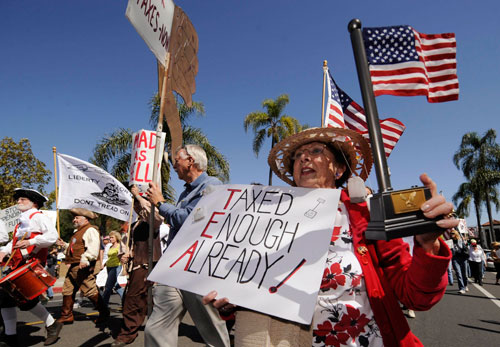 """On income tax day, right wing-sponsored protests (""""tea parties"""") are held across the country to condemn the president's economic agenda. Meanwhile, the Justice Department closes in on offshore tax cheats. Robert Scheer reports that former Senator Phil Gramm, their chief enabler, could be a target. (Reuters Pictures)"""