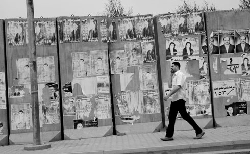 An Iraqi man in Baghdad walks by faded posters from the country's March 7 national parliamentary elections. Three months after the election, which saw millions of Iraqis from every city and faction brave mortars and rockets to participate in the multiparty vote, Iraq's politicians have still not approved a government.   In the weeks before voting day, the Supreme National Commission for Accountability and Justice marred the election's credibility by disqualifying more than 500 candidates because of alleged Baath party links—including several prominent Sunni and secular-minded Shiite politicians who were expected to do well in the election.  