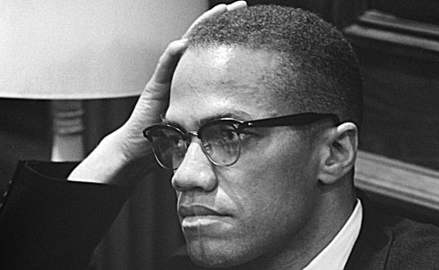 """A onetime street hustler involved in drugs, prostitution and gambling, Malcolm Little converted to Islam while in prison and, upon his release, became a leading minister of the Nation of Islam, a forceful advocate for black pride and a harsh critic of white racism. As Malcolm X, he inspired the Black Power movement, which competed with the integrationist wing of the civil rights movement for the loyalty of African-Americans, and wrote (with Alex Haley) the bestselling The Autobiography of Malcolm X. His father—an outspoken Baptist preacher and avid supporter of Black Nationalist leader Marcus Garvey—faced death threats from the white supremacist organization Black Legion and was killed in 1931. As a popular minister for the Nation of Islam, Malcolm X preached a form of black separatism and self-help. One of his recruits was boxer Muhammad Ali. In 1964, disillusioned by Nation of Islam leader Elijah Muhammad's behavior, Malcolm X left the organization. That year, he traveled to Mecca and, in his words, met """"all races, all colors, blue-eyed blondes to black-skinned Africans in true brotherhood!"""" When he returned to the United States he had a new view of racial integration. He was shot and killed on February 21, 1965, after giving a speech in Manhattan's Audubon Ballroom. Many suspect that Elijah Muhammad had a hand in his murder.   Further Reading: The Autobiography of Malcolm X. Malcolm X: A Life of Reinvention by Manning Marrable.     Credit: U.S. News & World Report Magazine Photograph Collection (Library of Congress)"""