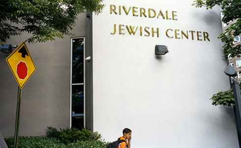"""A student passes by the location where, on May 20, 2009, James Cromitie and FBI informant Shahed Hussain placedthree inert explosive devices in a Mazda parked outside the Riverdale Jewish Center.The dummy bombs, composed of C-4, steel ball bearings and a timing device, were manufactured in an FBI lab and provided, through the informant, to the Newburgh Four. Hussain testified on September 8 that, once he and the Newburgh 4 arrived in Riverdale, he took complete control of the operation, as advised by FBI Supervisory Special Agent Robert Fuller. Though each of the Newburgh Four had previously been incarcerated, no man had ever been arrested for, or convicted of, a violent crime. Laguerre Payen, a Haitian national, has a 10 year history of mental illness and schizophrenia, and it remains unclear whether he was able to comprehend the plot. David Williams IV, as was shown in FBI recordings presented at trial, was hesitant to carry out the plot during the day, stating, """"What I'm saying is there could be people there. You don't want to hurt nobody.""""  © Lyric R. Cabral 2010"""