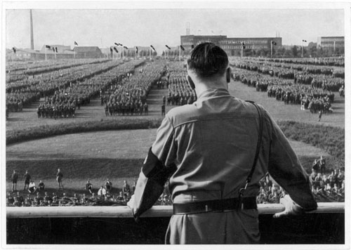 Hitler surveys his troops at a rally in Dortmund in 1933. Even as the German dictator takes aggressive action throughout Europe, many Americans fail to recognize how serious a threat his Nazi regime poses. [Mary Evans Picture Library/Everett Collection]