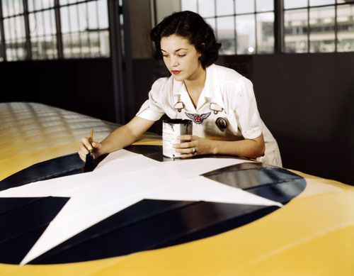 By 1942, the US can no longer sit on the sidelines. A civil service worker paints a US insignia on a Navy aircraft at a base in Corpus Christi, Texas.  [Everett Collection]