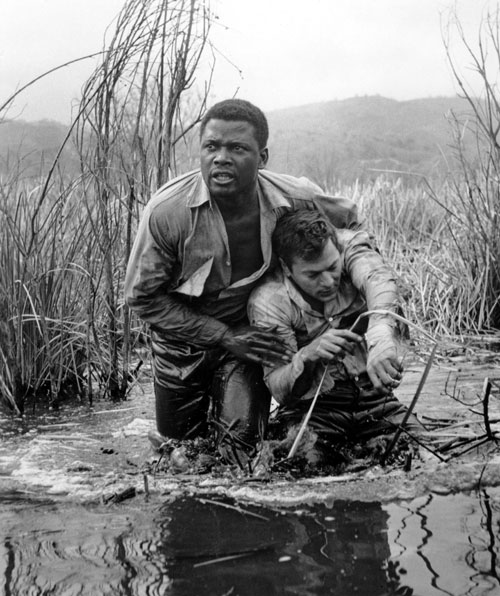 "Sidney Poitier and Tony Curtis play racially polarized fugitives from a prison chain gang in a melodrama that takes home the Best Screenplay Oscar. Critic Robert Hatch calls the film ""first-rate entertainment"" but pointedly reminds Nation readers that the film fails to delve deep enough into the ugly realities of racism and prejudice. (Photo: Everett Collection)"