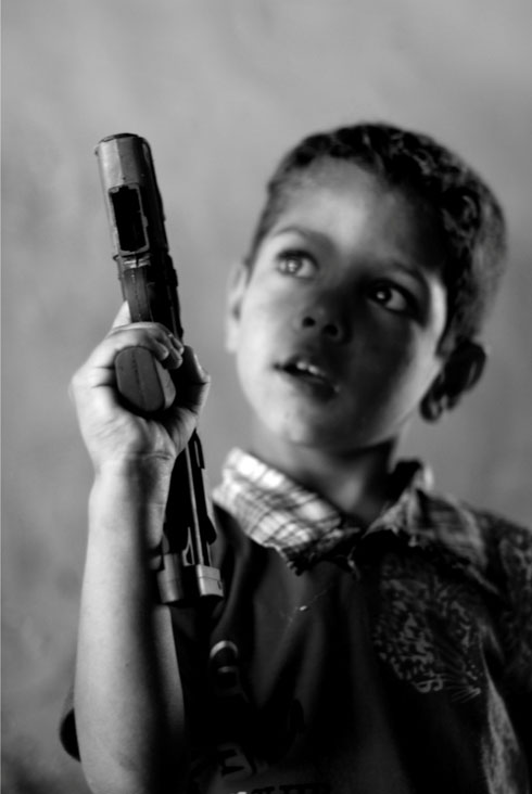 """A boy, aged 5, plays with one of his few possessions, a toy gun, in a squatter camp in Baghdad. In 2006, his father, a Sunni, was killed by a car bomb in the town of Abu Ghraib. After his death, the neighborhood elder warned the boy's mother that she was in imminent danger because she was a Shiite living in a Sunni neighborhood. """"Yes, I know your sons are Sunni, but you are still in danger. We are not able to protect you,"""" the elder said, according to the boy's mother.  Credit: Samer Muscati/Human Rights Watch"""