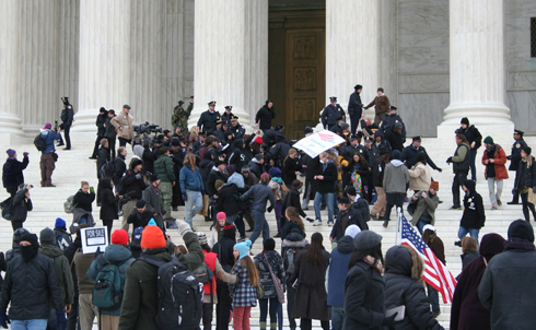 Some protesters pressed through the line of police who were blocking the stairs to the front doors of the Supreme Court.  Image credit: Loren Fogel