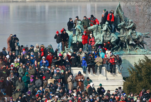 People made good use of a statue near the National Mall to get a better glimpse of inaugural activities. (AP Photo/Mark Wilson, Pool)