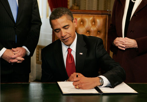 """In his first official action, Obama signs a proclamation declaring Tuesday a national day of renewal and reconciliation. When reporters remarked that he was left-handed, the President replied, """"Get used to it.""""  (Reuters Photos)"""