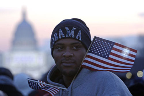 Sean Scott of Bridgeport, Conn., sports Obama gear and a flag as he awaits the start of the inaugural events in Washington. (AP Photo/Matt Rourke)