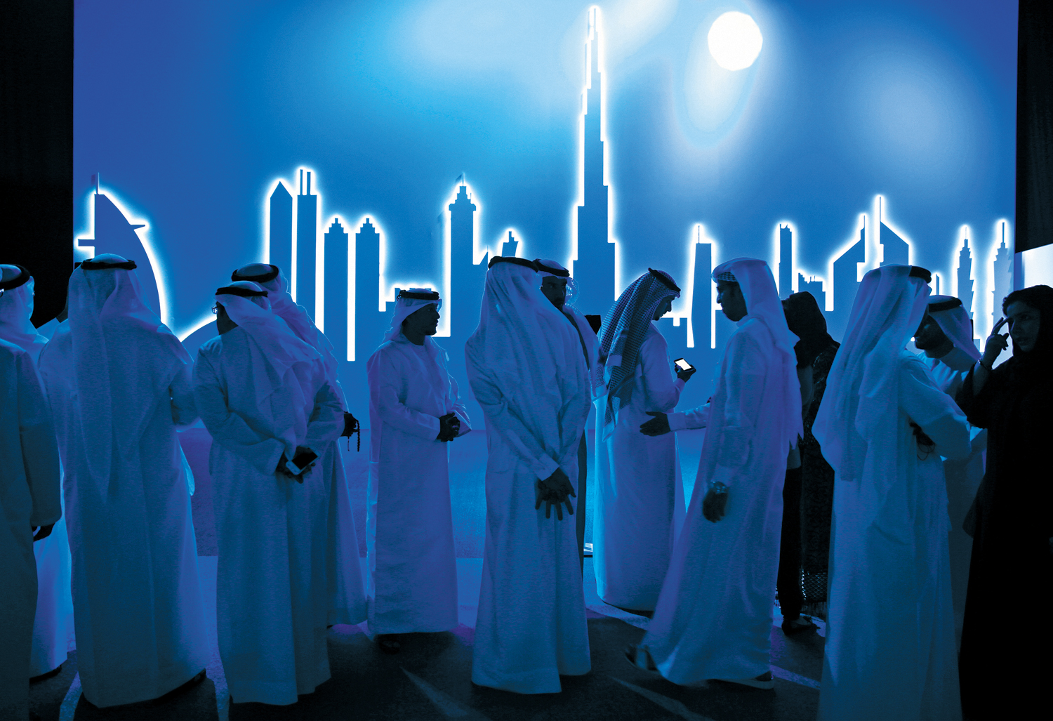 Emirati-attendees-wait-in-front-of-an-image-of-the-city's-skyline-in-Dubai-on-March-5-2014