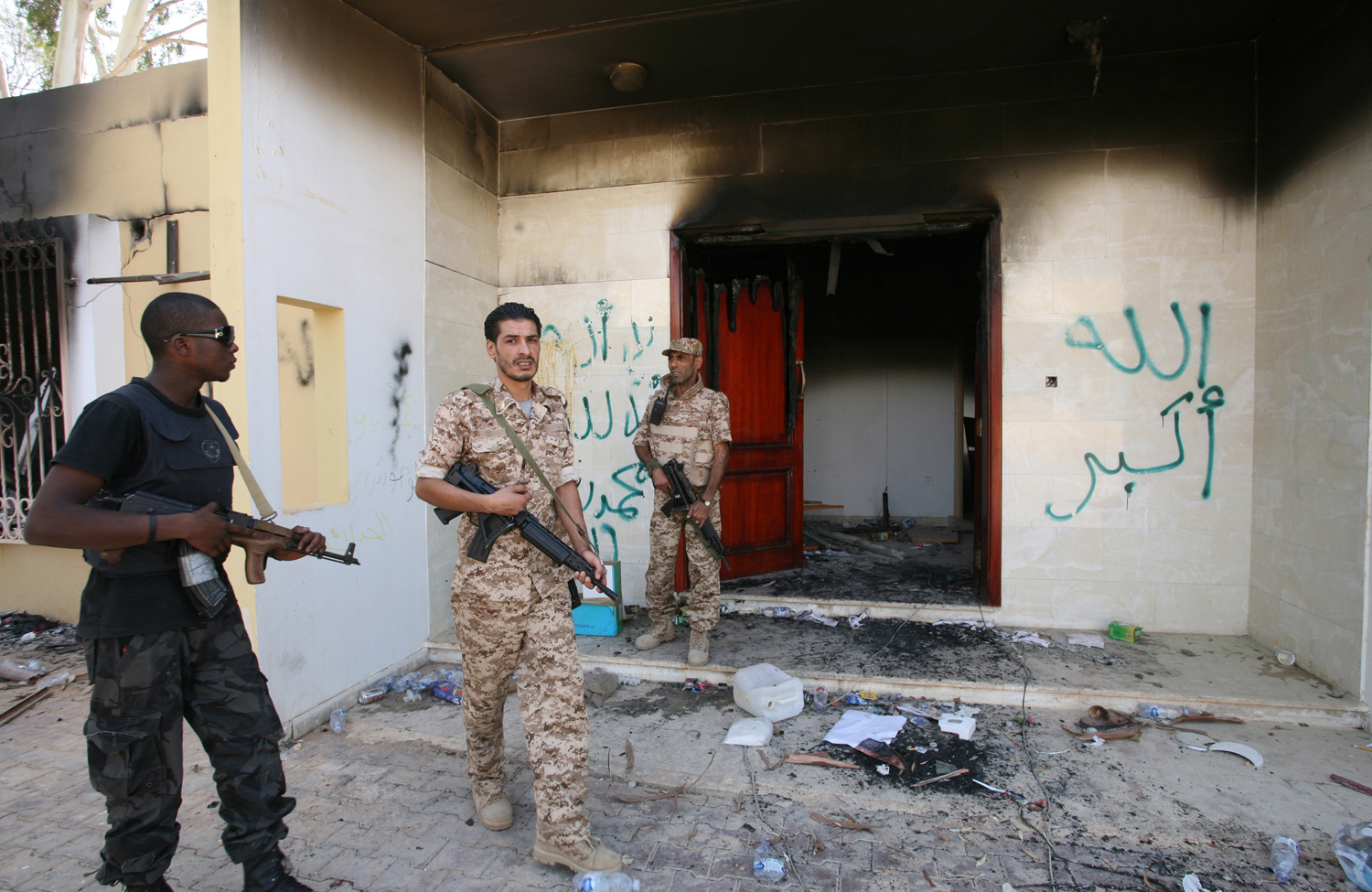 Libyan-military-guards-check-one-of-the-U.S.-Consulates-burnt-out-buildings-during-a-visit-by-Libyan-President-Mohammed-el-Megarif.-AP-Photo