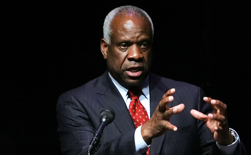 """One of Supreme Court Justice Clarence Thomas's major contributions to the battle against democracy has been his advocacy to do away with Section 5 of 1965's Voting Rights Act. In a 2009 dissenting opinion, Thomas argued that the section—which requires states covered by the act receive pre-clearance from the Justice Department or a three-judge District Court in Washington for any election law changes that affect minority voters—is a band-aid in search of a wound, because intentional discrimination in voting """"no longer exists.""""  Credit: AP Images"""