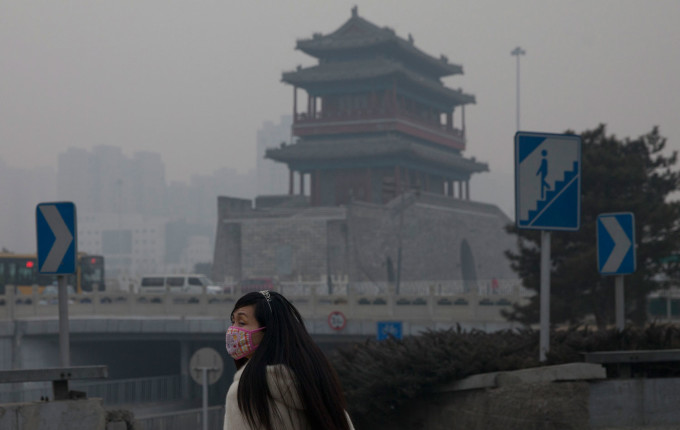 A woman wears a mask as she walks on a polluted day in Beijing, China. (AP Photo/Alexander F. Yuan)