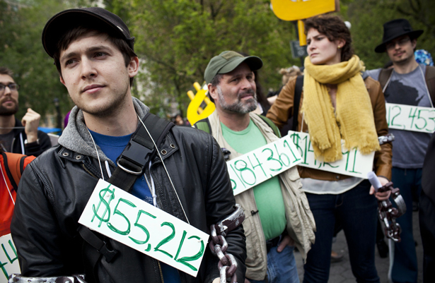 32df4149aec Occupy Wall Street demonstrators participating in a street-theater  production wear signs around their neck representing their student debt  during a protest ...
