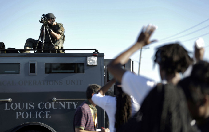 A member of the St. Louis County Police Department points his weapon in the direction of a group of protesters in Ferguson, Missouri on Wednesday, August 13, 2014. (AP Photo/ Jeff Roberson)