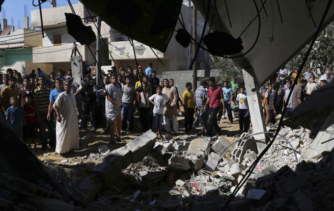 Palestinians gather around a house which police said was destroyed in Israeli air strikes in Khan Younis in the southern Gaza Strip, July 8, 2014. (Reuters/Ibraheem Abu Mustafa)