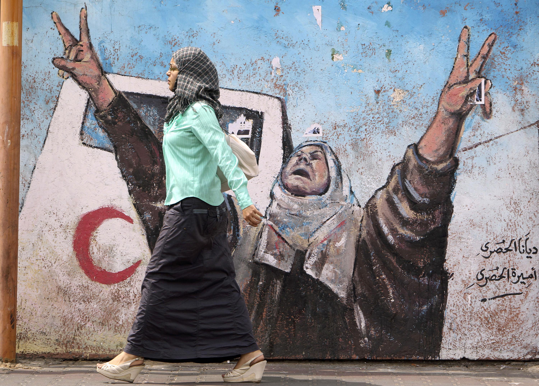 Palestinian-woman-walks-by-mural