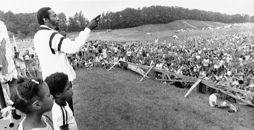 """Comedian Dick Gregory addresses a crowd of about 4,500 people who gathered to protest the building of the Seabrook Nuclear Power Station during the Fourth Annual Clamshell Alliance demonstration in 1979. Harvey Wasserman described the group in his Nation article as """"the most controversial anti-nuclear group on the American scene."""""""