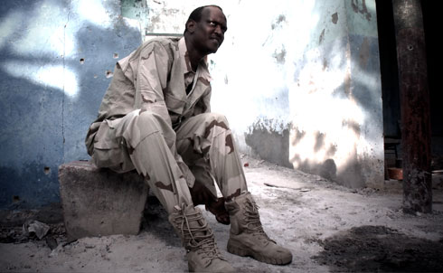 "Noor puts on a new pair of combat boots near a frontline where his forces fought the Shabab in Mogadishu. Noor has guided the transformation of ASWJ from a nonviolent, quasi-political organization to a paramilitary group. His militia has received support and training from Ethiopia and a private security firm, Southern Ace, which was accused by the UN of ""egregious"" violations of an arms embargo on Somalia.