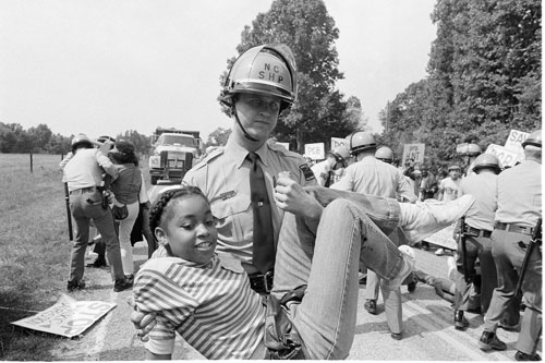 """A policeman carries a protester to a waiting van, after she and 39 others tried to block trucks carrying toxic chemicals in North Carolina in 1982. In a Nation article published four years later, Seth Zuckerman discovers that on """"Environmentalism's 16th birthday,"""" there are two camps fighting for a greener future: environmental lobbying groups based in DC and grassroots protesters, both of whom scorn the other."""