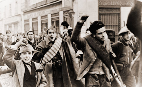 """In the last years of the 1930s, the world's attention turned to Spain, where the great ideological battles of the twentieth century were fought with bullets, bombs and bluster. The Civil War pitted Socialists, Anarchists and defenders of the Republic against Monarchists and Fascists in a struggle that drew in forces from all over the Western world. In 1937, The Nation published a letter from a twenty-year-old member of the Abraham Lincoln Brigade, the American volunteer battalion that sided with the Republican cause """"to fight against the fascists and landlords and the foreigners who send the bombing planes"""" over Spanish houses.  Everett Collection"""